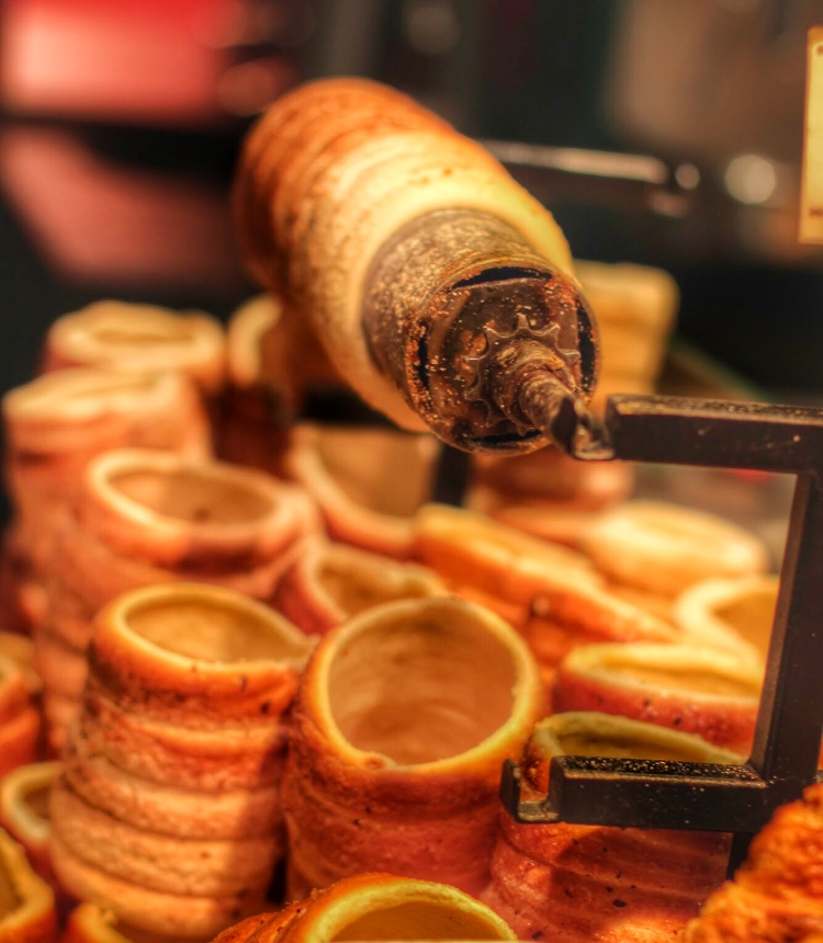 Trdelnik freshly baked on the special cylinder cooking utensil.