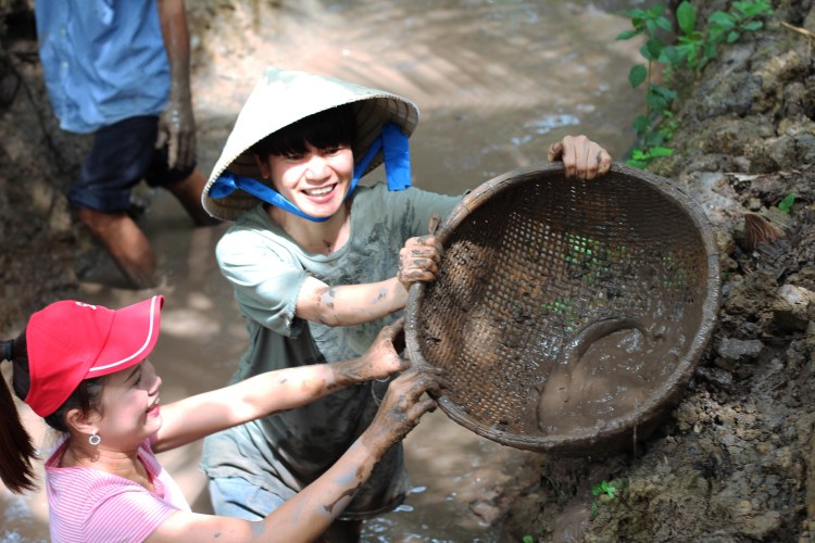 Catching your own fish with a basket, one of the like-a-local activities you can enjoy in Mekong Delta. This one I tried with my colleagues in Bến Tre, Vietnam.