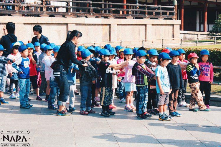 Kindergarten kids waiting in line for school field trip.